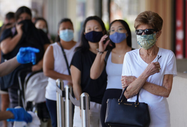 Customers line up socially distanced outside Kahala Whole Foods during COVID-19 pandemic. August 5, 2020