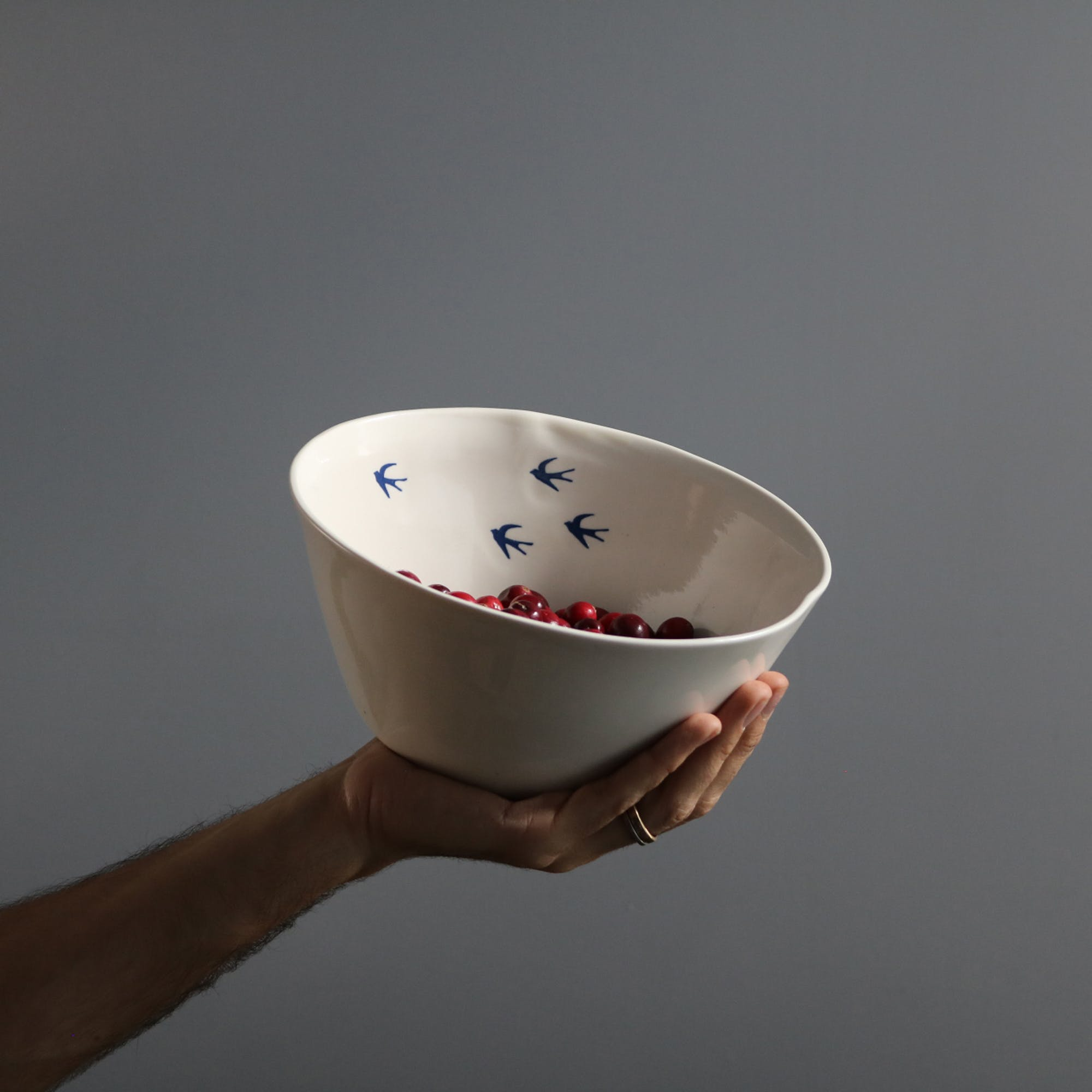 Picked by GOOP as a small luxury for the Mom going a million miles an hour, this porcelain Serving Bowl in a soft white features pretty blue swallows to remind us to return home as often as they do.