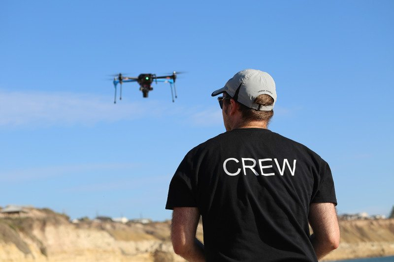 Man with drone in the background hovering above the sand