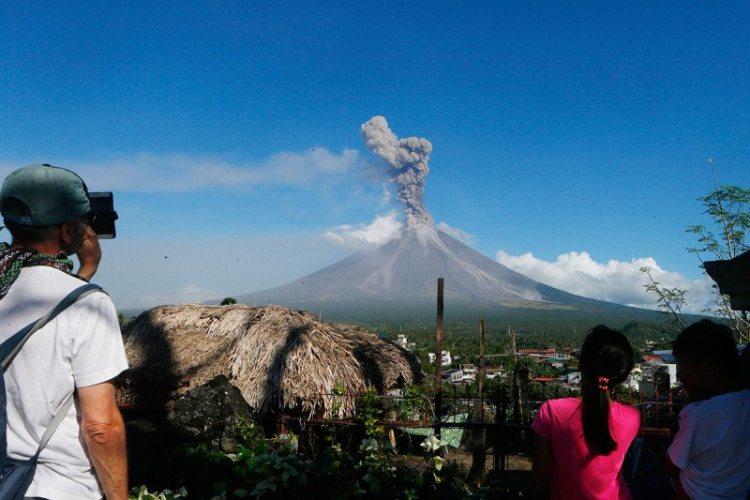 Gli spettatori guardano da una distanza di sicurezza mentre il vulcano erutta i pennacchi di cenere nell'aria