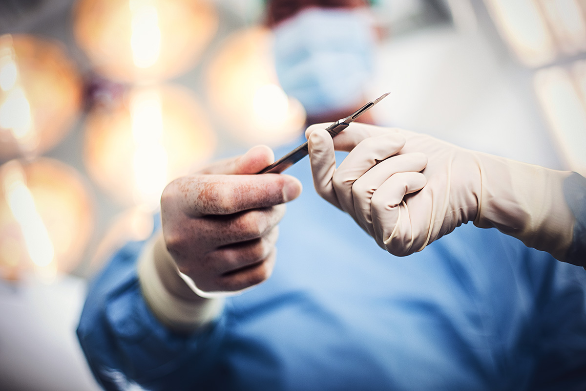A surgeon passing a surgical implement to a colleague