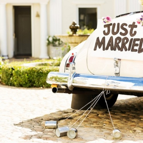 Just Married Sign And Cans Attached To Car