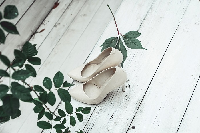 white wedding shoes in the rain on a white wooden table