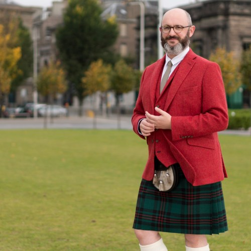 Chris wearing his bespoke kilt, with a red jacket and waistcoat