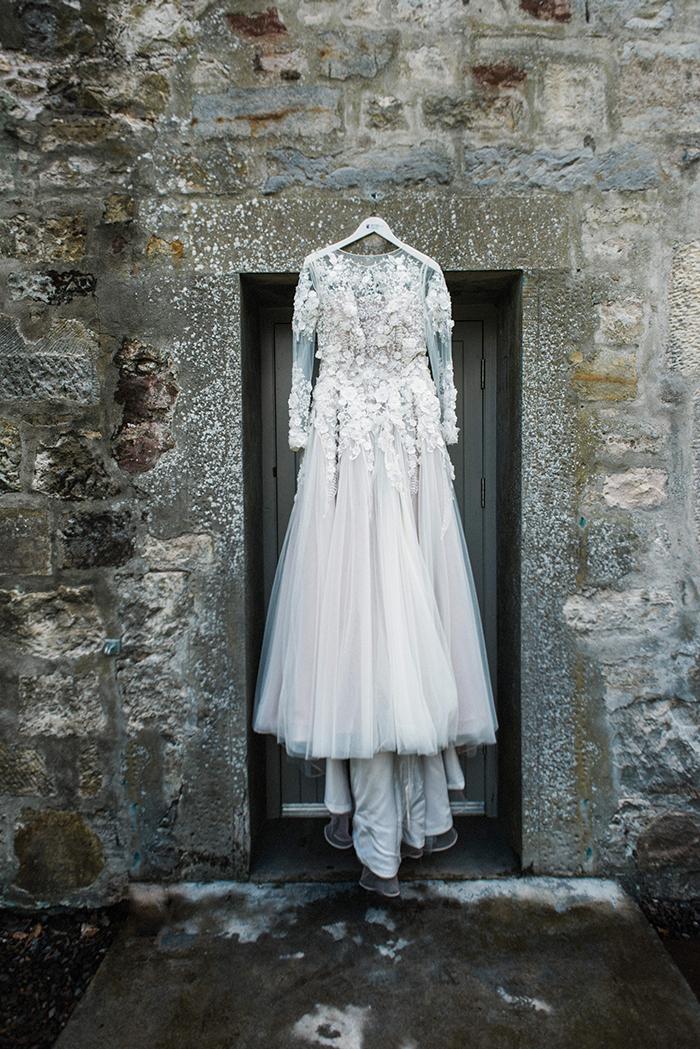 Photos by Zoe rustic PapaKåta tipi wedding - bride dress hanging up