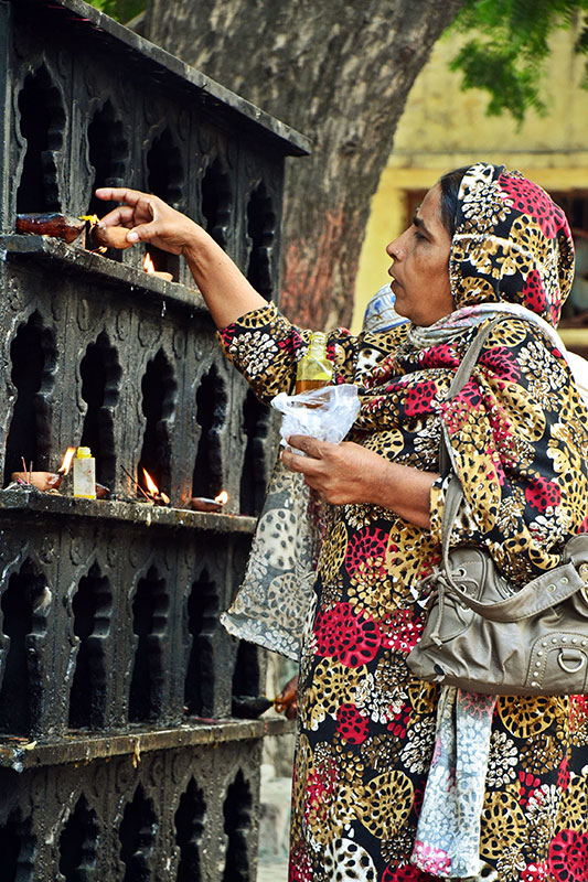 A woman lights a diya, a ritual often seen at Sufi shrines in the Indian sub-continent. Photo by Abdullah Khan.