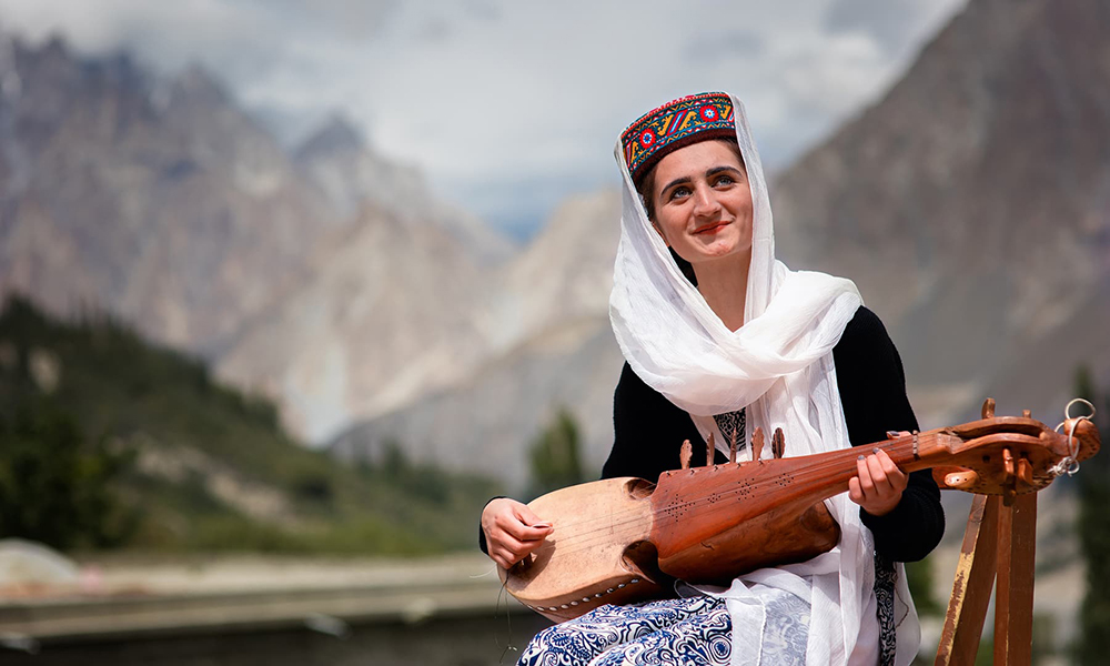 A girl smiles as she plays the traditional instrument, rabab.