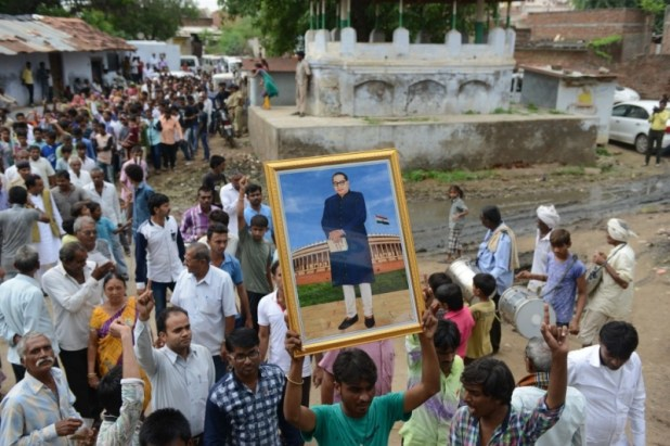 A supporter of the Dalit community holds up the image of BR Ambedkar during the Dalit Asmita Yatra rally in Valthera village near Ahmedabad, Gujarat, on August 6, 2016. (Photo credit: AFP/Sam Panthaky).