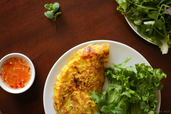 A single serving of banh xeo with a side of fish sauce | HungryHuy.com