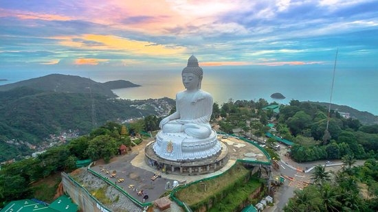Giant Buddha Statue in Phucket Thailand with cloud filled skies and ocean in the background