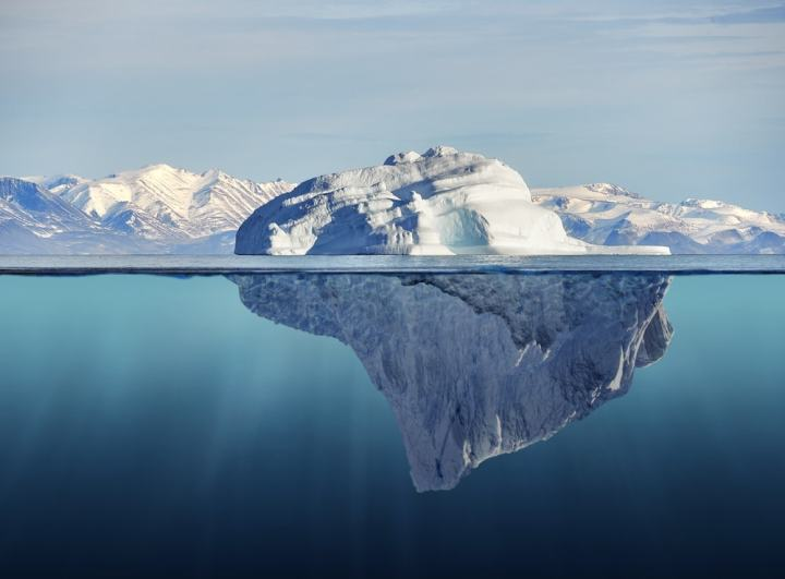 Photograph of ice berg in water, half above and half below the surface