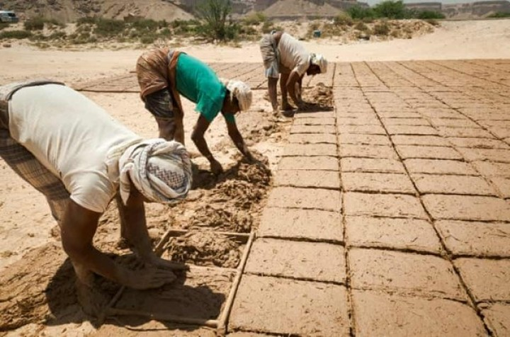 Three men baking mudbricks to maintain the 500 year-old skyscraperson the outskirts of Shibam in the sun, wearing their traditional Yemeni clothes i