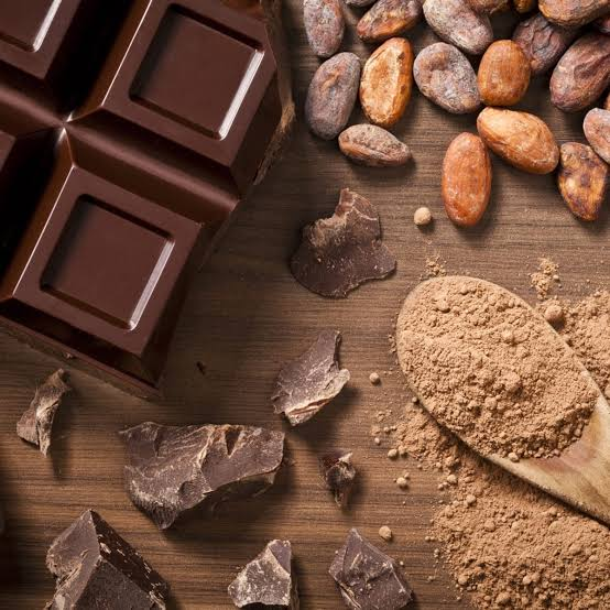 The Cocoa beans are crushed into Cocoa powder as seen in the picture, with a solid chocolate bar next to it