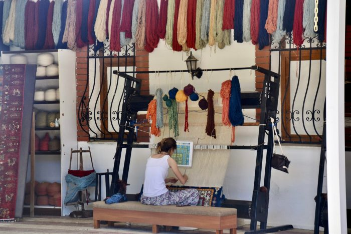 Woman seated at a carpet loom weaving a design. Red, green, navy blue, and yellow silk yarns hang above her head.