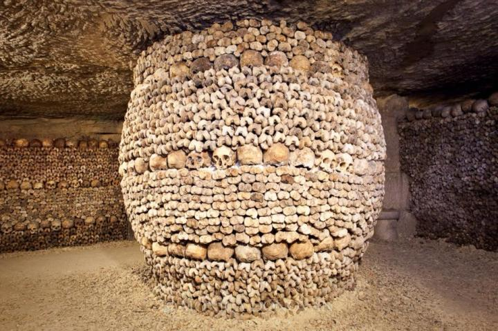 A circular column made up of skulls stands in the middle of the room on a stone floor where the rest of the walls are made up from skulls dark tourism.