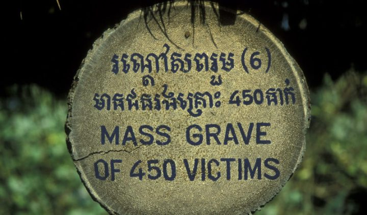 A circular stone tablet with the words 'Mass Grave of 450 victims' engraved on it in English at the bottom and in Cambodian on the top.