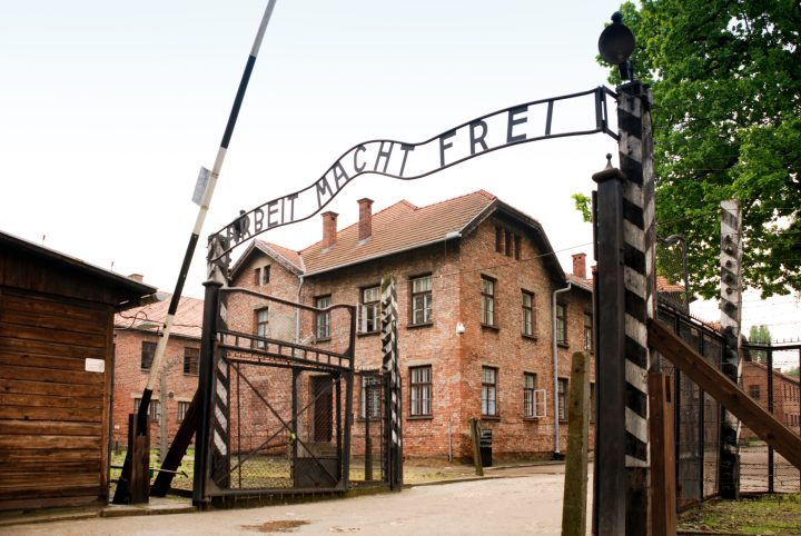 A red brick building stands to the left behind rusted iron gates with the words Arbeit Macht Frei written like a banner over the entrance. dark tourism