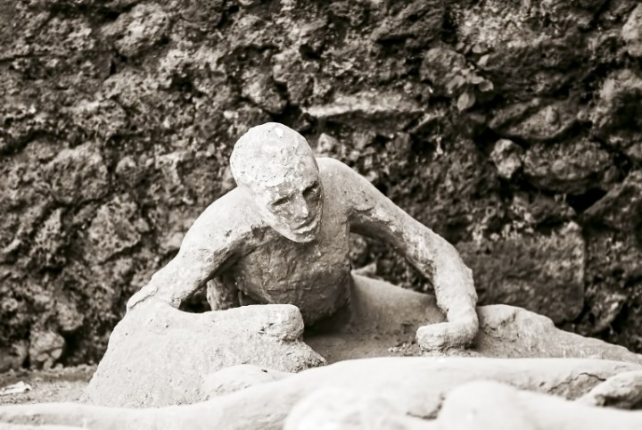 A white plaster cast of a man with half formed limbs clings on to the side of a stone wall