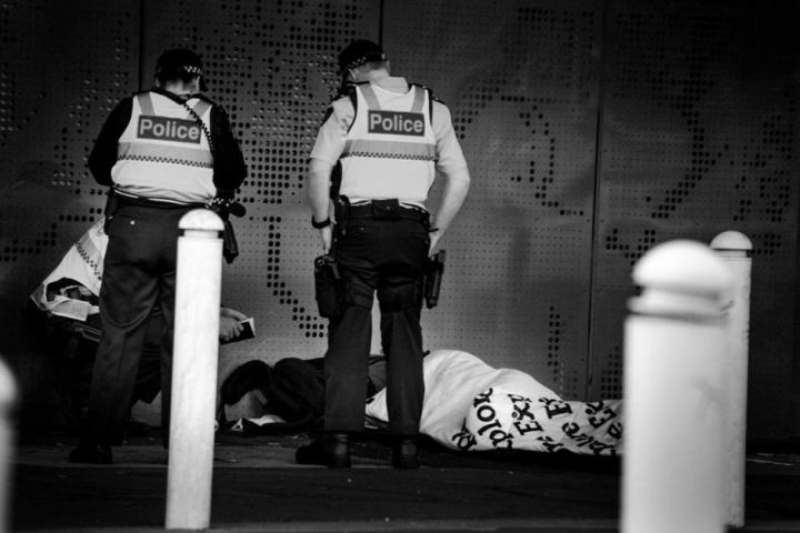 Black and white image of two police officers standing over a homeless person lying on the concrete floor in a sleeping bag