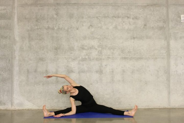 A woman stretching. Stretching also helps with recovery, just like a plant-based diet