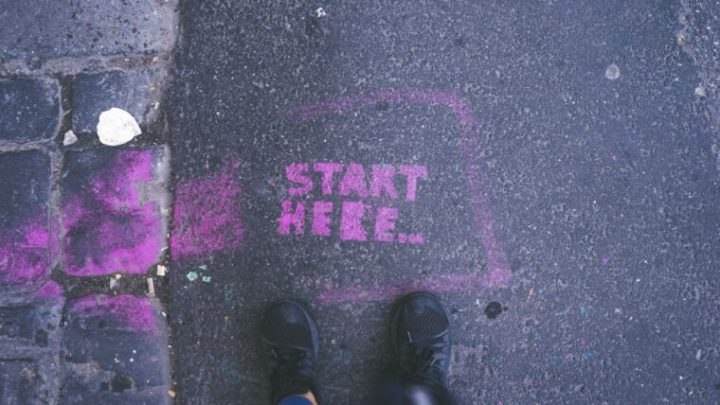 """""""Start here"""" sprayed on a street. As easy as it is to just start here with your journey to being plant-based."""