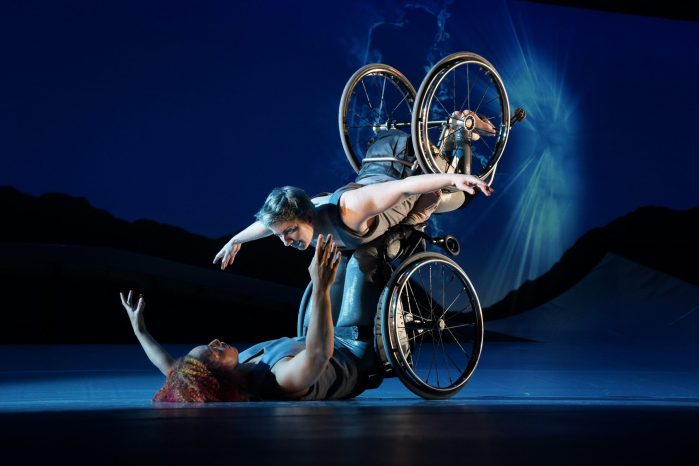 an image of a stage performance of two disabled artists with wheelchairs, as one is lying down on her back, the other one leans on her wheelchair opening her arms