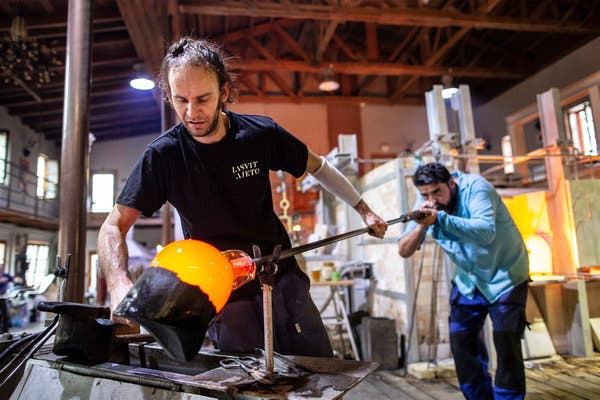 glassmaker blowing molten glass and shaping it