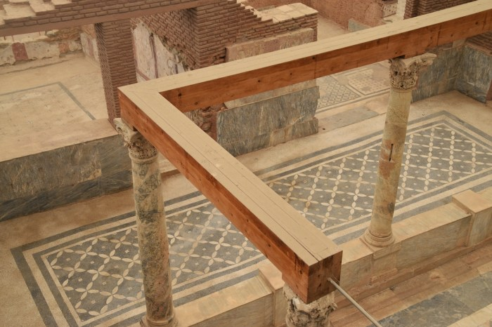 Inside view of an excavated terrace house in Ephesus. A dark gray mosaic covers the floor of a hallway in a diagonal pattern, and narrow marble columns support wooden beams to an adjoining room.
