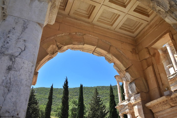 Underneath the Gate of Mazaeus and Mithridates in Ephesus. Marble columns support the giant stone archway. Green pine trees cover the hillside under a bright blue sky.