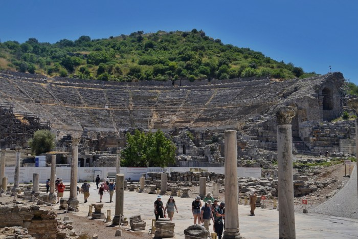 The theatre at Ephesus, built into the hillside. Columns line a stone paved street in the foreground.
