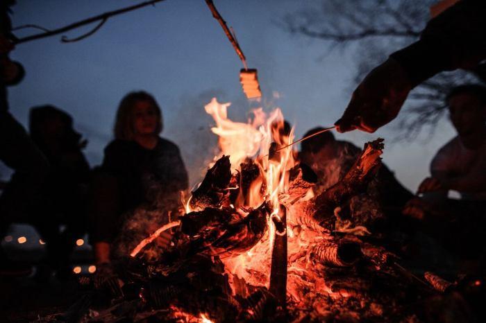 People sitting around a fire; photo credit: qvc.co.za