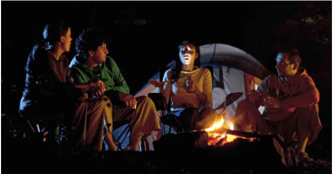 A group of men sitting around a campfire, listening to a girl telling stories with flashlight in her hand.