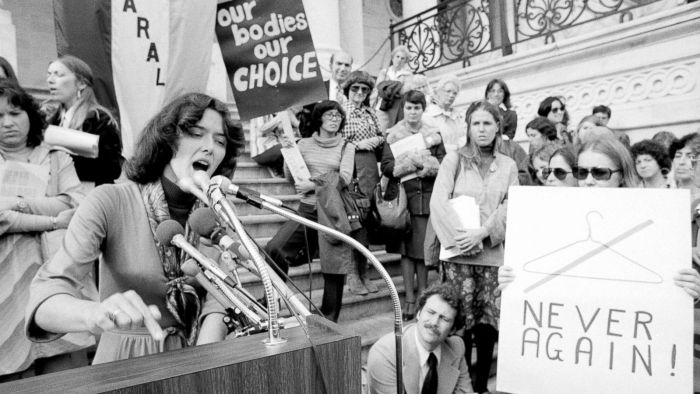 Black and white image of a courtroom in the 1970s shows a woman speaking into a microphone at the stand and people holding signs surrounding her adocating against abortion law