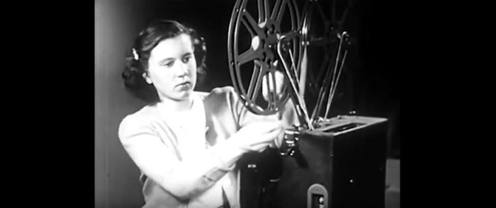 Image of female film editor reading a reel.