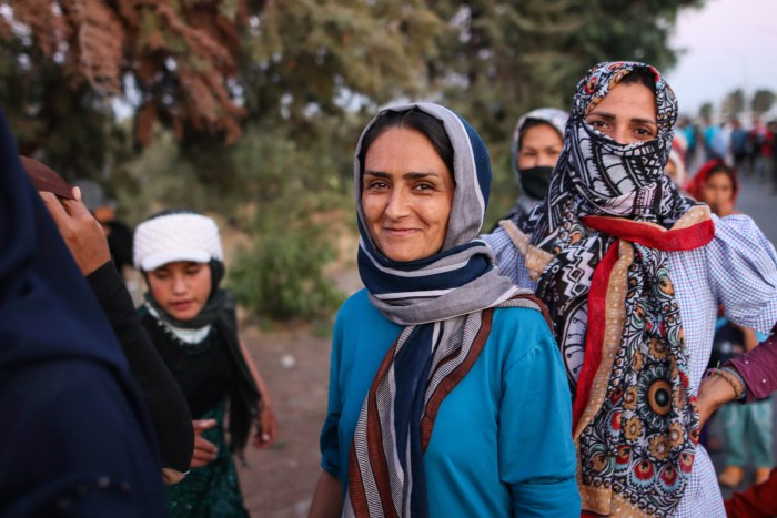 An Afghan woman dressed in blue smiles at the camera with a child to her left and two other women to her right