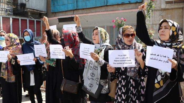 A group of Afghan women stand in a line holding paper signs advoacting for women's rights