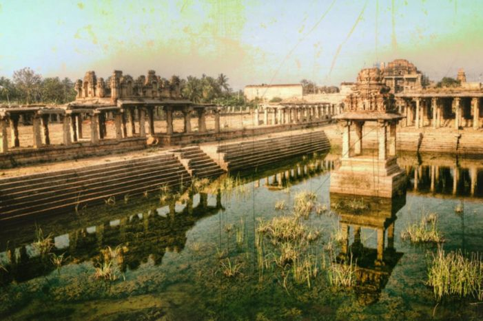 A colour photograph of a inside of a temple, the middle shrine surrounded by green, murky water, while the remaining architecture stands as it was built in Ancient India.