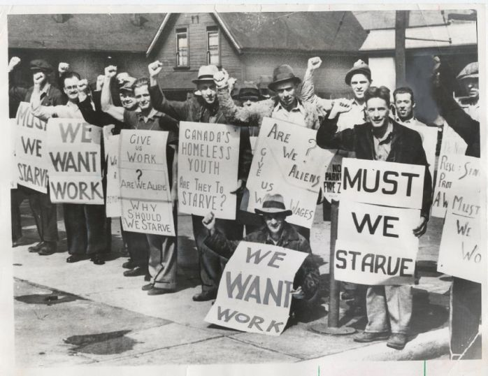 The photograph of protesting unemployed workers in the 1930s. All of them are holding signs demanding the government to provide them with jobs. Some signs read: