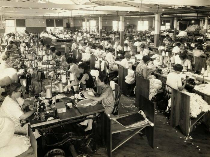 The photograph of the operating room of Ladies Rayon Undergarment Factory, 1920. It portrays multiple large tables with women at work seated on their both sides.