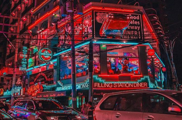 Red neon lights line a street filled with shops, near a road packed with cars. Cafes, diners and bars are being advertised by these lights, inviting guests to stop by.