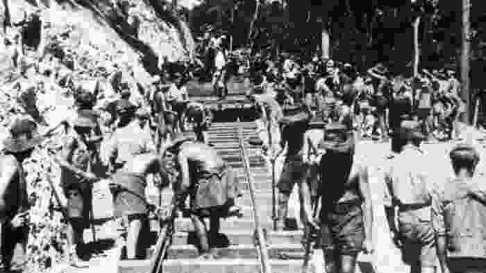 A black and white image of the early stages of building the railway, where POWs and Southeast Asian laborers are working hard in the sun in Siam, supervised by Korean and Japanese soldiers.