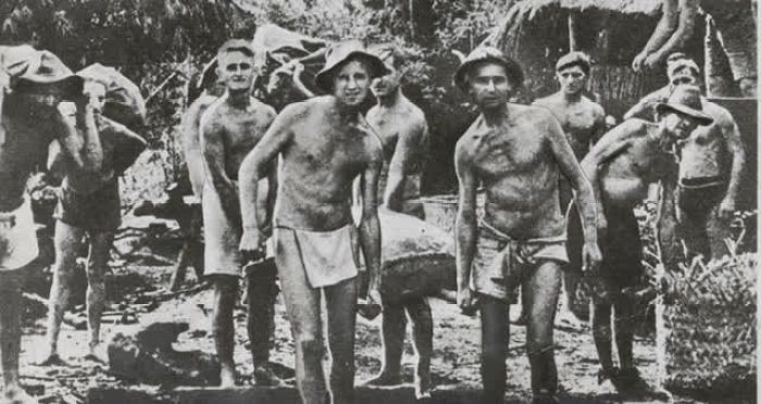 A black and white image of POWs carrying their equipment from their camp towards the railway, where they will continue their work in Siam. Some barely have their uniforms, just enough to cover below their waist, while covered in dirt and close to malnourished.