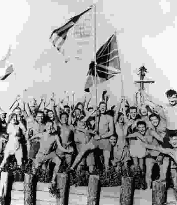 A black and white photograph of the POWs from different Allied countries, waving their country's flags and screaming for joy when hearing the news that the war is over.