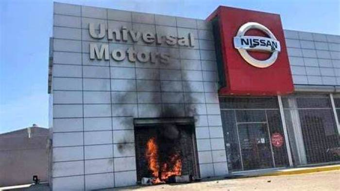 a colored image of a Nissan building set on fire by black people