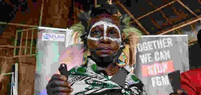 A photo of a Kenyan renowned traditional circumciser Regina holding a razorblade.