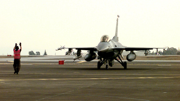 Staff Sgt. Rodney Johns marshals an F-16CJ Fighting Falcon to a parking spot at Incirlik Air Base, Turkey, after an Operation Northern Watch mission enforcing the northern no-fly-zone over Iraq on Jan. 11, 1999.