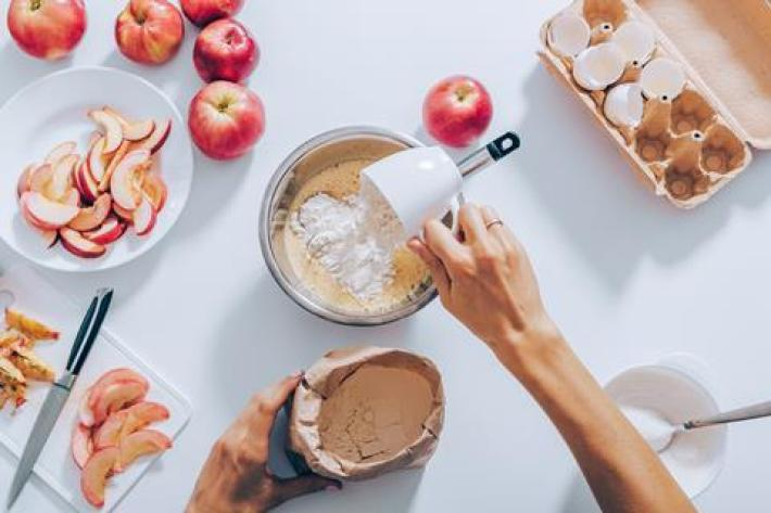 A photo from above of someone adding a cup of flour to a mixing bowl