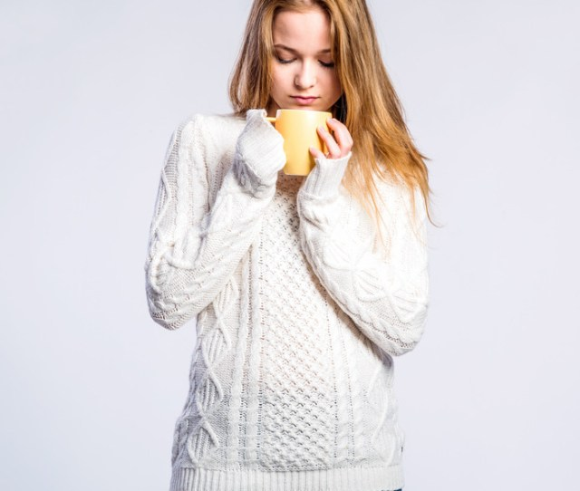 Teenage Girl In Jeans And White Sweater Holding A Cup With Hot Drink Young Woman Studio Shot On Gray Background