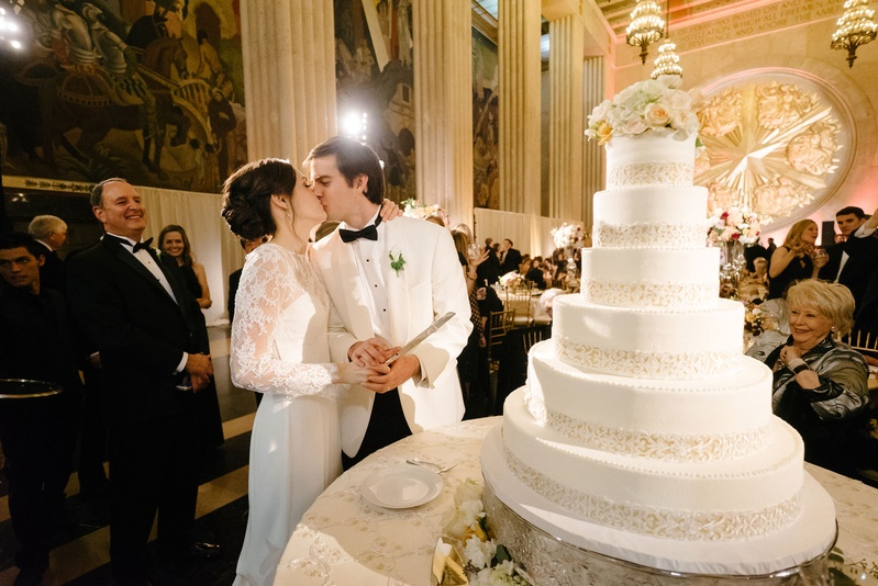 Cakes   Desserts Photos   Kiss During NYE Cake Cutting   Inside Weddings wedding reception cake cutting new year s eve bride in long sleeve illusion  lace dress kissing groom
