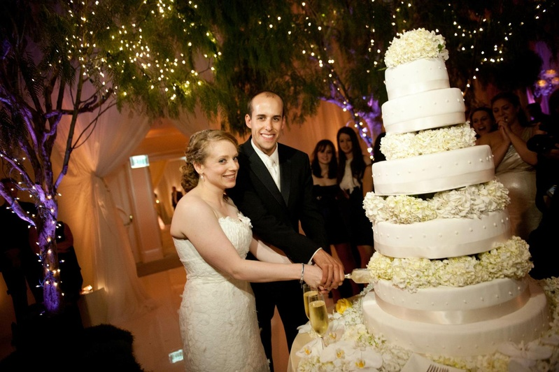 Cakes   Desserts Photos   Traditional Cake Cutting   Inside Weddings Bride and groom cut into towering wedding cake